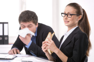 Employees eating and sneezing at their desks at work